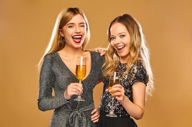 Mujeres sonrientes felices en elegantes vestidos glamorosos con copas de champán