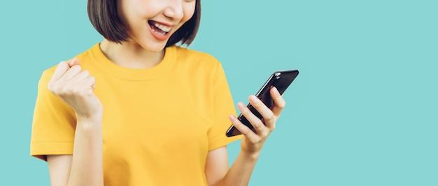 Mujeres sonrientes felices y sosteniendo un teléfono inteligente con asombrado por el éxito