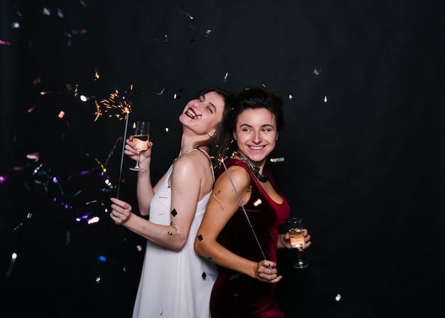 Mujeres sonrientes jovenes que se colocan de espaldas con las luces y los vidrios de bengala