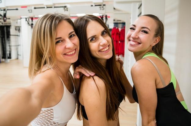 Mujeres sonrientes juntas en el gimnasio