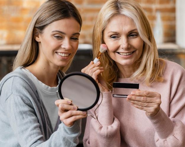 Mujeres sonrientes maquillándose en casa