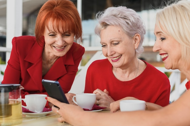 Mujeres sonrientes mirando un teléfono