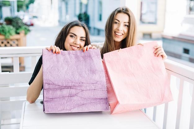 Mujeres sonrientes que muestran bolsas de papel