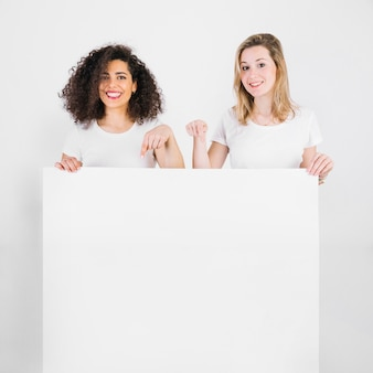 Mujeres sonrientes que señalan en el cartel en blanco