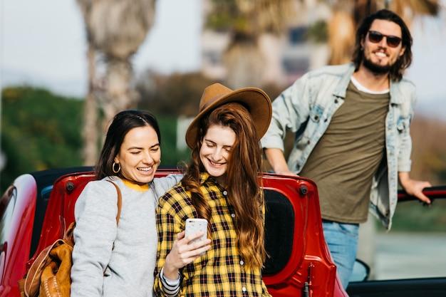 Mujeres sonrientes que toman autofotos en un teléfono inteligente cerca del maletero del coche y el hombre que se inclina hacia fuera del auto