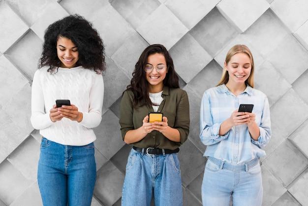 Mujeres sonrientes que usan móviles