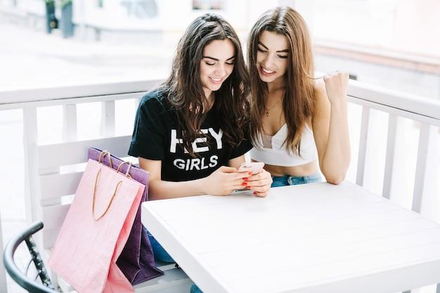 Mujeres sonrientes que usan smartphone en café