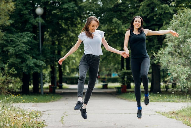 Mujeres sonrientes saltando y tomados de la mano