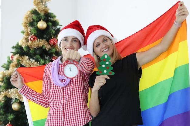 Las mujeres sonrientes sostienen la bandera lgbt y el reloj de alarma en el fondo de las tradiciones familiares del árbol de navidad