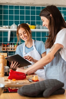 Mujeres sonrientes en tiro medio de cocina