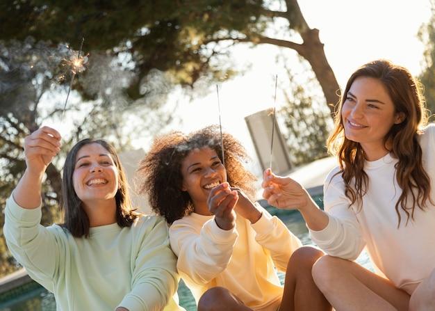 Mujeres sonrientes con tiro medio de fuegos artificiales