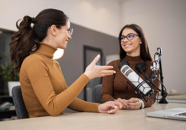 Mujeres sonrientes transmitiendo en radio juntos