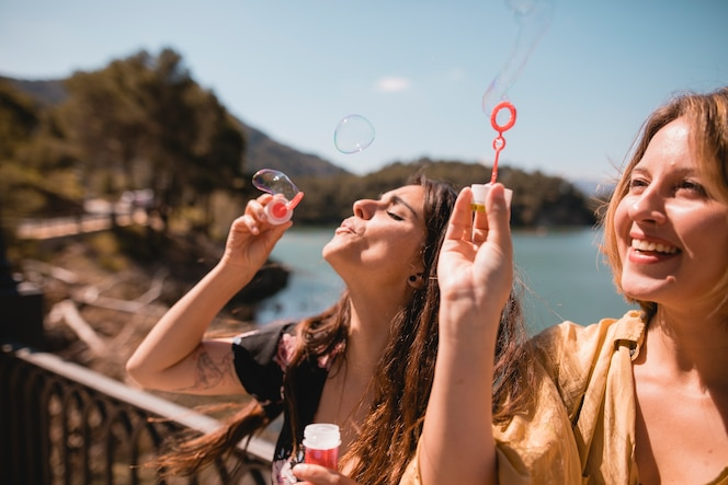 Mujeres soplando y atrapando burbujas