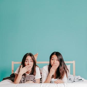 Mujeres sorprendidas acostada en la cama
