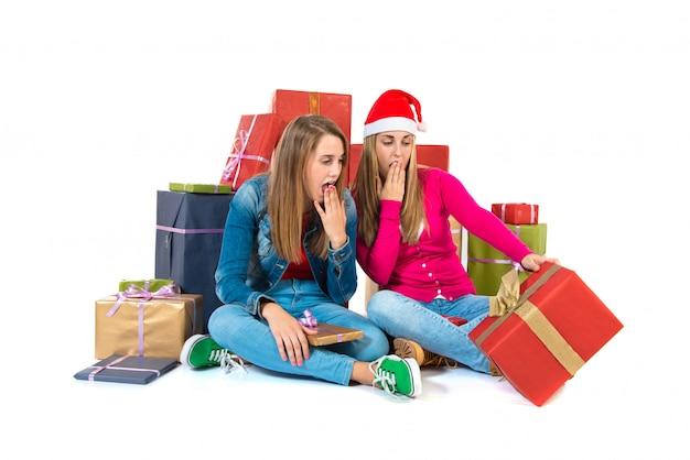 Mujeres sorprendidas de la navidad que sostienen los regalos sobre el fondo blanco