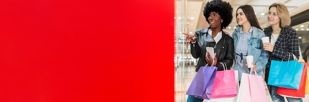 Mujeres sosteniendo bolsas de compras con espacio de copia
