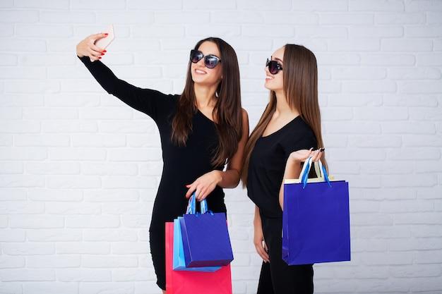 Mujeres sosteniendo bolsas negras en la luz en el viernes negro de vacaciones