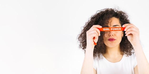 Mujeres sosteniendo la cinta de poder chica cerca de los ojos