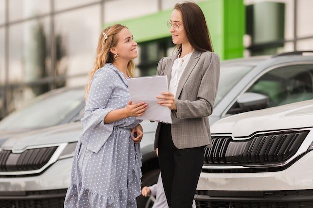 Mujeres sosteniendo un contrato y mirándose