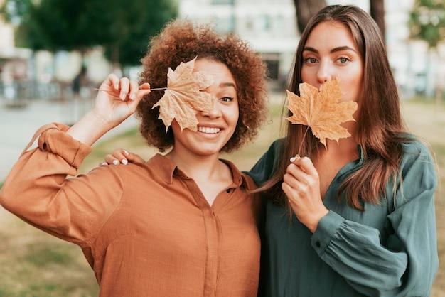 Mujeres sosteniendo hojas secas en otoño