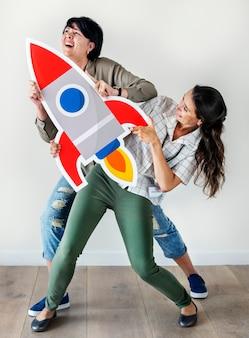 Mujeres sosteniendo el icono de cohete