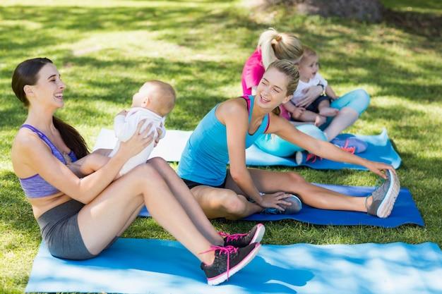 Mujeres sosteniendo a sus bebés mientras hacen ejercicio
