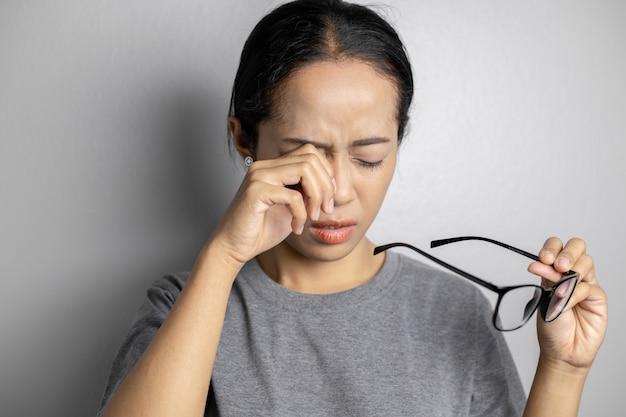 Las mujeres sostienen gafas y sufren dolor en los ojos.