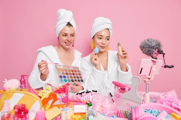 Las mujeres sostienen la paleta de sombras de ojos y el frasco de base hablan sobre hacer maquillaje profesional grabar video en línea tienen su propio blog vestidas con albornoces toallas en la cabeza.