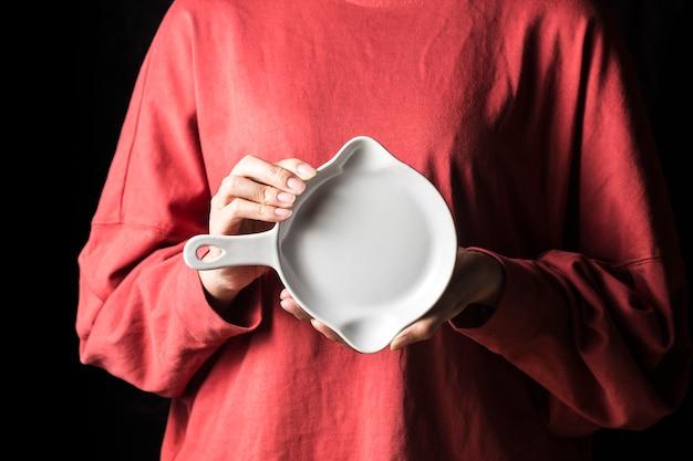 Las mujeres sostienen platos blancos en sus manos.