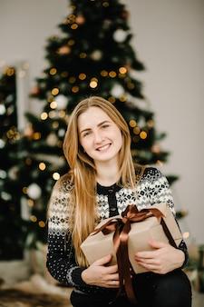 Las mujeres sostienen el regalo de navidad o la caja de regalo decorada de año nuevo feliz navidad y felices fiestas