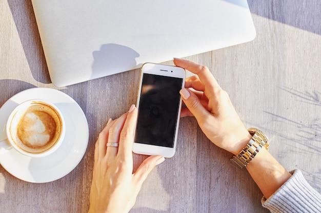 Las mujeres sostienen el teléfono inteligente durante el descanso para tomar café en un café