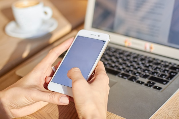 Las mujeres sostienen el teléfono inteligente durante la pausa para el café en un café