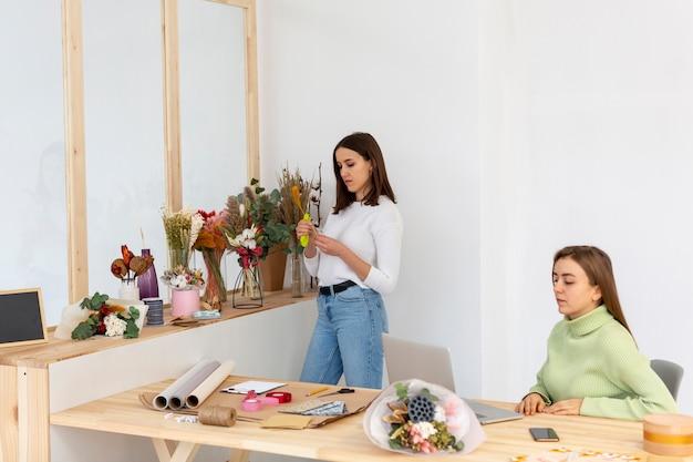 Mujeres en su florería creando sus planes de inversión.