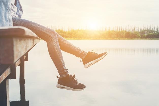 Las mujeres de talle bajo con pies que pone en el lago se relaja con su día de fiesta