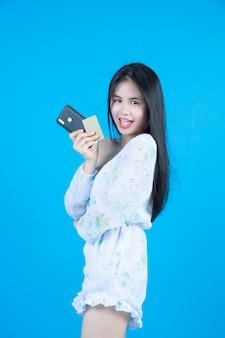 Mujeres con tarjetas inteligentes y teléfonos móviles en gris