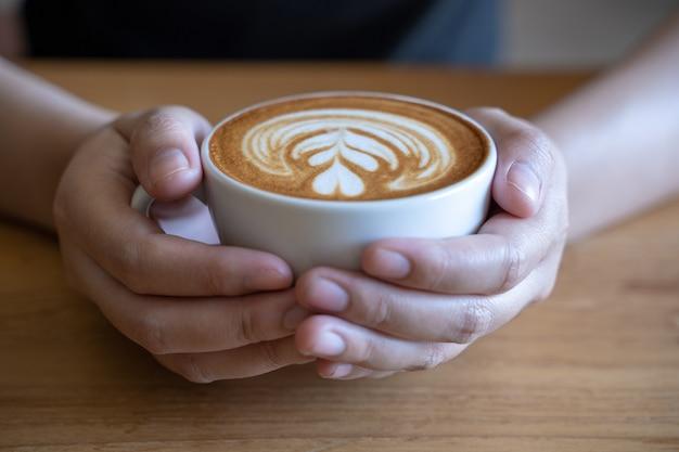 Mujeres con taza de café, mesa de madera, café mientras toman café