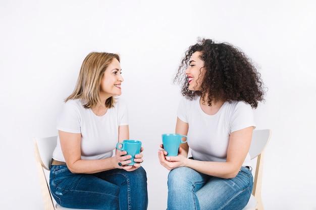 Mujeres con tazas sonriendo y hablando