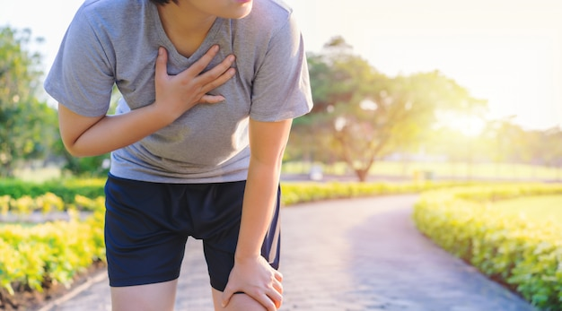 Las mujeres tienen dolor en el pecho mientras corren en el jardín.