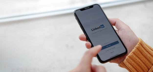 Las mujeres tienen un teléfono inteligente con la aplicación de linkedin en la pantalla