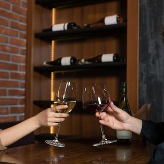 Las mujeres tintinean copas de vino en el bar.