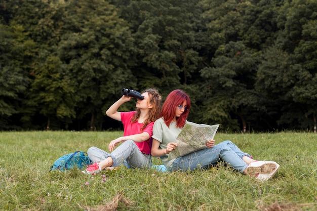 Mujeres de tiro completo con binoculares y mapa