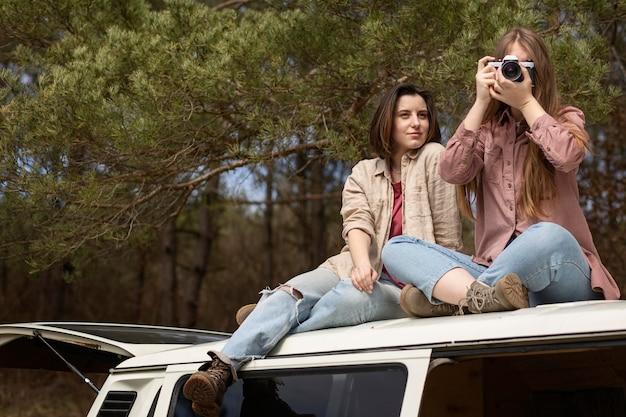 Mujeres de tiro completo con cámara de fotos
