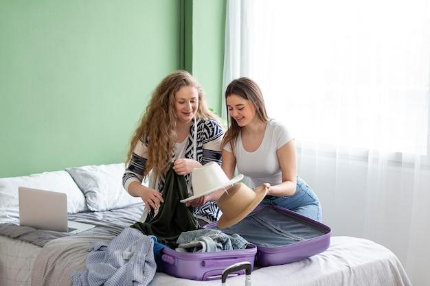 Mujeres de tiro completo empacando en casa