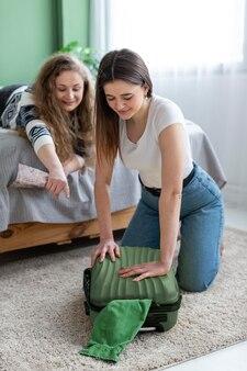 Mujeres de tiro completo empacando juntos en el interior