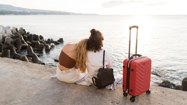 Mujeres de tiro completo con equipaje rojo