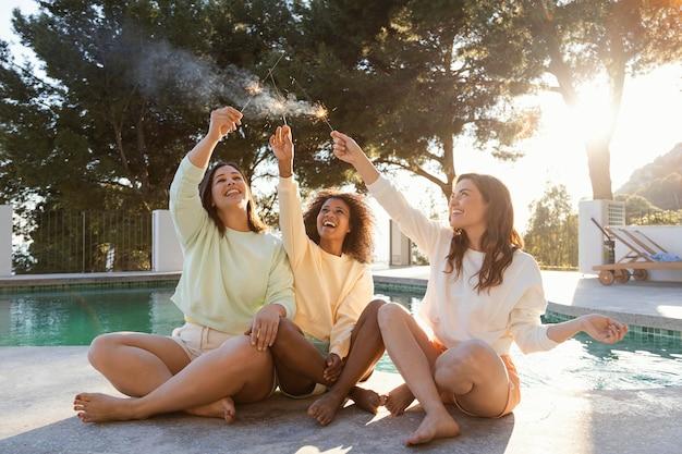 Mujeres de tiro completo con fuegos artificiales