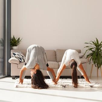 Mujeres de tiro completo haciendo yoga juntos