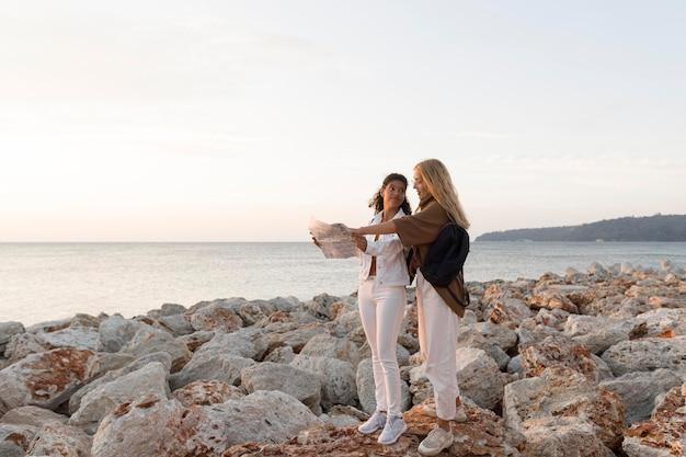Mujeres de tiro completo mirando el mapa