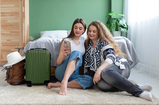 Mujeres de tiro completo sentados en la alfombra