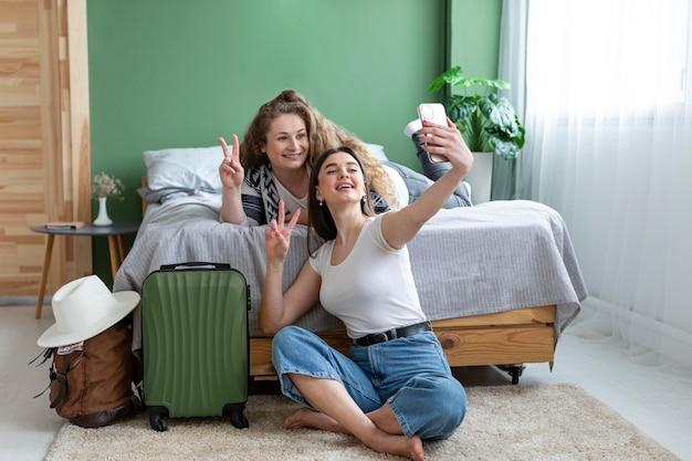 Mujeres de tiro completo tomando selfies juntas